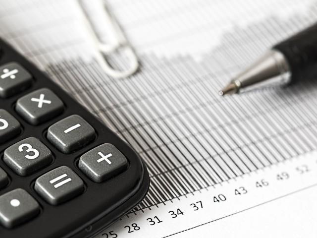 Taschenrechner und Stift auf einer Kalkulationstabelle